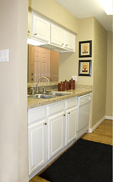Impressive remodeling of galley-style kitchen features sanded, repainted and refaced sink and overhead cabinets and upscaled granite laminate countertops.