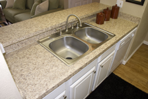 Remodeled double-sink granite laminate with pass-through bar countertops and white refaced raised-panel cabinetry increase tenat marketing appeal, property value and investment return for owners.