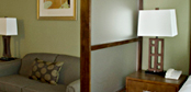 Custom wood and frosted glass sectional screens for hotel guest rooms.