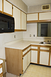 Before: Dated and worn yellow oak cabinets with white laminate door facings and exposed hinges and white laminate countertops.
