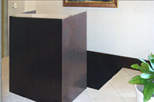 Small relocatable registration cabinet-style desk, custom built with dark wood-stained finish and granite countertop.